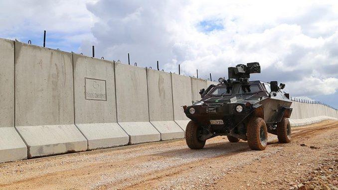 مركبة مدرعة بقرب جدار تركي