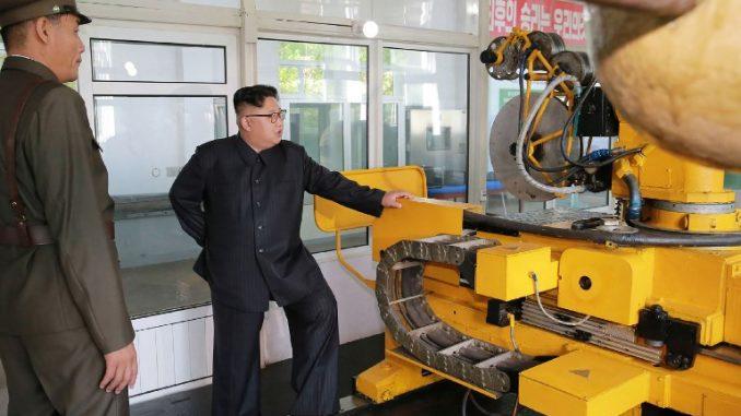 صورة للرئيس الكوري الشمالي إلى جانب مكوّنات الصاروخ الجديد (AFP)