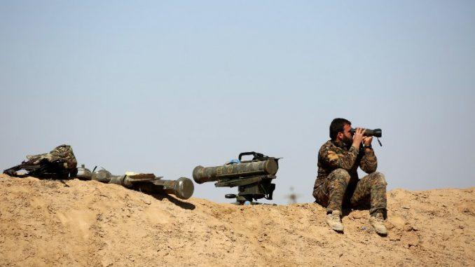 مقاتل من القوات السورية الديمقراطية المدعومة من الولايات المتحدة يستخدم منظار وهو جالس بجانب أسلحة مضادة للدبابات في قرية صباح الخير على الضواحي الشمالية لدير الزور في شباط/فبراير 2017 (AFP)