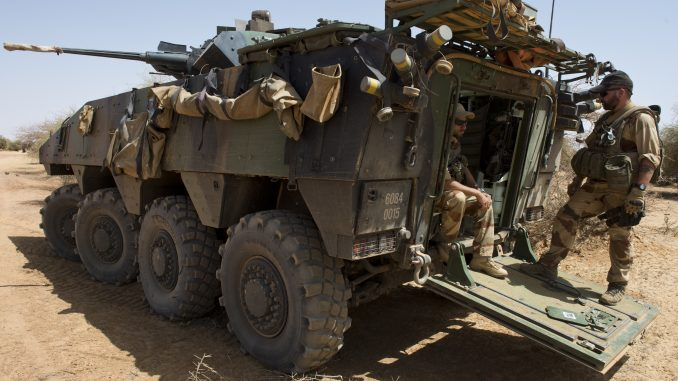جنود فرنسيون من فوج المشاة 92 يقفون إلى جانب عربتهم المدرعة من نوع VBCI في حين تمر قافلة عسكرية فرنسية إلى قرية أماكولادجي شمال غاو في 10 مارس 2013، لتقييم احتياجات السكان المحليين هناك (AFP)