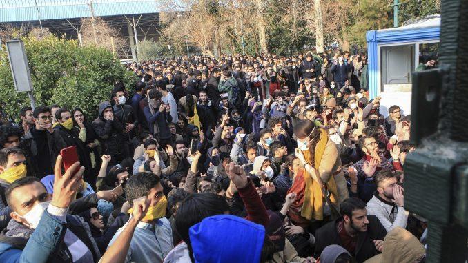 طلاب إيرانيون يحتجون داخل جامعة طهران في حين تعمل الشرطة الإيرانية لمكافحة الشغب على استخدام القنابل المسيّرة للدموع في طهران، إيران في 30 كانون الأول/ديسمبر 2017 (AFP)