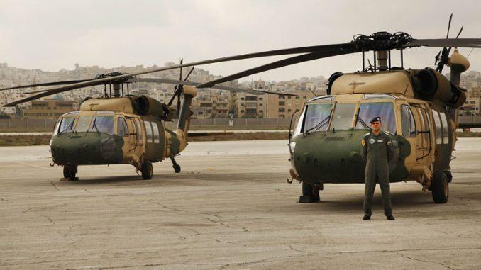 """القائد طارق المغيرة يقف أمام طائرتي هليكوبتر من طراز UH-60A، تعرفان باسم """"بلاك هوك""""، سلّمتها الولايات المتحدة للأردن في مطار ماركا في عمان، في 3 آذار/مارس 2016 (AP)"""