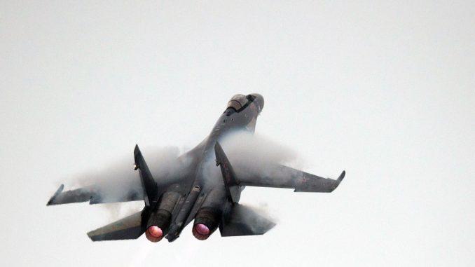 """طيار روسي يقود مقاتلة """"سوخوي-35"""" خلال رحلة تجريبية قبل معرض الين للطيران 2014 في تشوهاي بمقاطعة قوانغدونغ بجنوب الصين يوم 10 تشرين الثاني/نوفمبر 2014 (AFP)"""