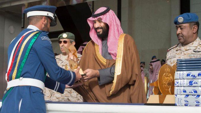 صورة وفّرها القصر الملكي السعودي في 21 فبراير/شباط 2018 تُظهر ولي العهد السعودي محمد بن سلمان وهو يُقدّم سيفاً لأحد التلاميذ الخريجين الجدد في سلاح الجو خلال حفل للصف 93 لطلاب أكاديمية الملك فيصل الجوية في العاصمة الرياض (AFP)