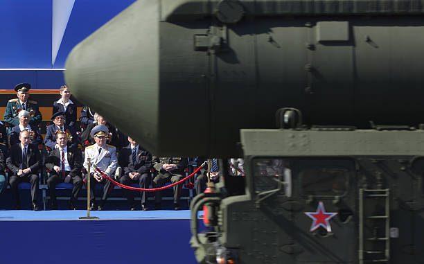 """الرئيس الروسي فلاديمير بوتين (إلى اليسار) و ورئيس الوزراء ديمتري ميدفيديف (إلى اليمين) يشاهدان عرض يوم النصر في الساحة الحمراء في موسكو، في 9 أيار/مايو 2013، في حين تمرّ قبالتهما قاذفات الصواريخ البالستية العابرة للقارات """"توبول"""" (AFP)"""