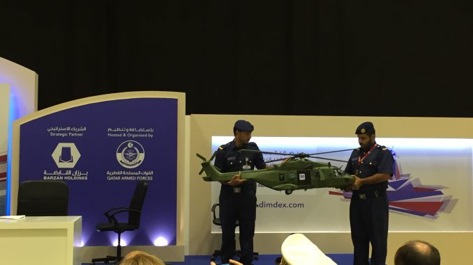 عنصران من القوات الجوية الأميرية القطرية يحملان نموذج عن مروحية NH90 المخصصة لقطر خلال حفل توقيع الاتفاق (الأمن والدفاع العربي)