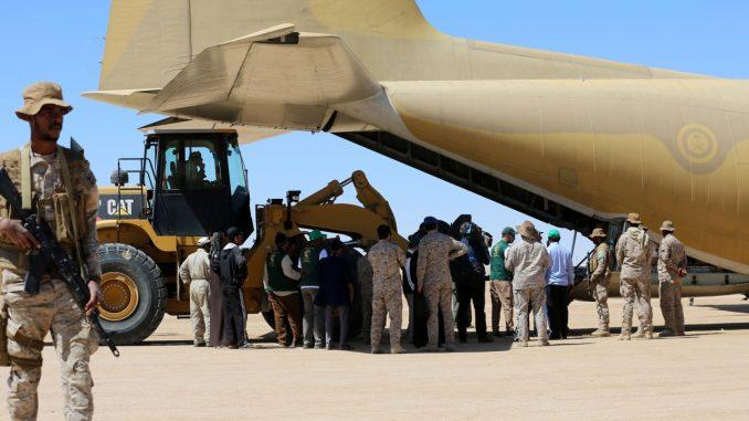 جنود سعوديون يقفون حراساً في حين يفرغ العاملون مساعدات من طائرة شحن تابعة لسلاح الجو السعودي في مطار في مأرب المركزي في اليمن في 8 شباط/فبراير 2018 (AFP)