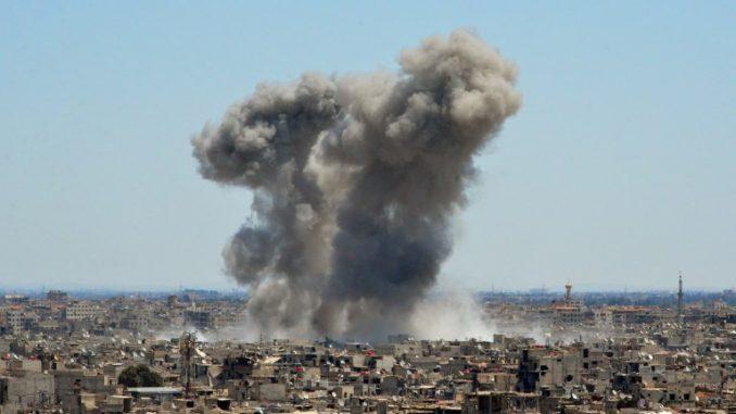 صورة تم التقاطها خلال جولة للحكومة بالقرب من حي القدم الجنوبي بدمشق، تُظهر دخاناً يتصاعد من المباني في مخيم اليرموك، وهو مخيم للاجئين الفلسطينيين على أطراف العاصمة، والمناطق المحيطة به، خلال قصف النظام الذي يستهدف جماعة الدولة الإسلامية (داعش) في 24 نيسان/أبريل 2018 (AFP)