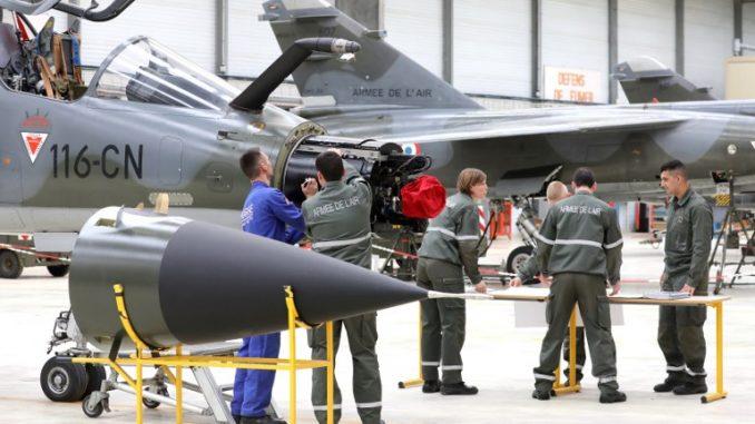 """طلاب عسكريون يقفون إلى جانب مقاتلة """"ميراج أف 1"""" في مدرسة الضباط التابعة للقوات الجوية المتوسطة (EFSOAA) قبل زيارة الرئيس الفرنسي للاحتفال بالذكرى الأربعين للمدرسة في قاعدة سلاح الجو الفرنسي في سان أجنانت في 14 حزيران/يونيو 2018 (AFP)"""