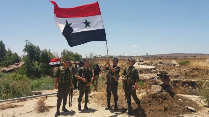 صورة تم نشرها من قبل وكالة الأنباء السورية الرسمية (سانا) في 26 تموز/يوليو 2018 تُظهر جنود الجيش السوري يحملون العلم الوطني في قرية الحميدية في محافظة القنيطرة الجنوبية (AFP)