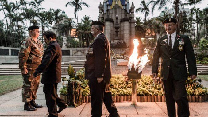ضباط الطاقم من محميات الدفاع التابعة لقوة الدفاع الوطني لجنوب أفريقيا (SANDF) يضيئون مصباح غاز مضاء في القبر المقدس في ديربان، في 11 تشرين الثاني/نوفمبر 2018 كجزء من الاحتفالات بالذكرى المئوية لصدور الهدنة في 11 نوفمبر 1918 وانتهاء الحرب العالمية الأولى (AFP)