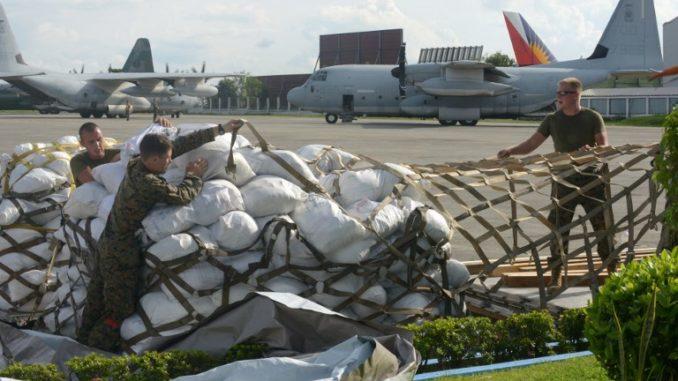 قوات المارينز الأميركية تحضر مواد الإغاثة قبل أن يتم تحميلها على طائرة KC-130 لضحايا الإعصار هايان سوبر في تاكلوبان، في قاعدة عسكرية في مانيلا في 14 تشرين الثاني/نوفمبر 2013 (AFP)